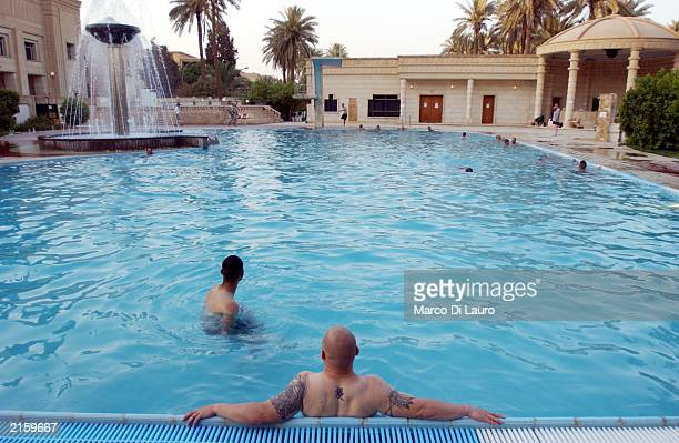 Off duty US soldiers enjoy Saddam Hussein's swimming pool at the Republican Palace July 14 2003 in Baghdad Iraq