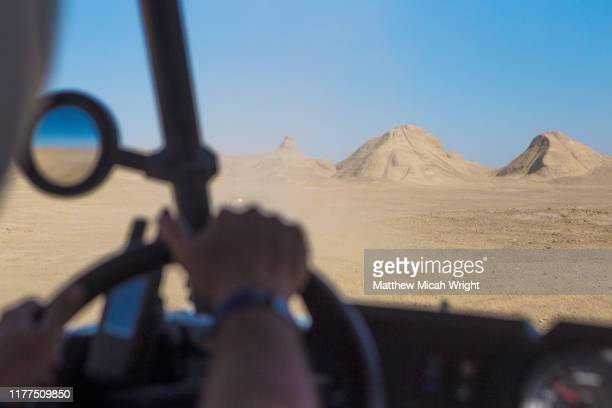 off road racing through the desert. a bike climbs a mountain - motorsport stock pictures, royalty-free photos & images