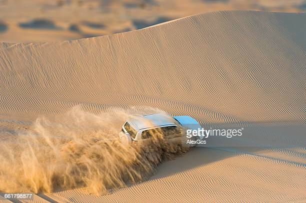 Off road vehicle driving through desert, Abu Dhabi, UAE