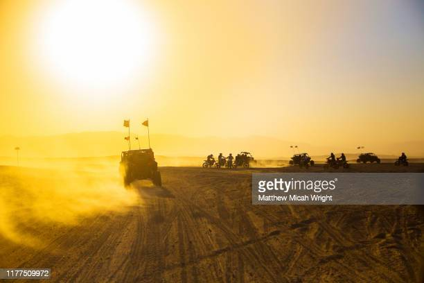 atv off road vehicles race through the desert. - escaping stock pictures, royalty-free photos & images