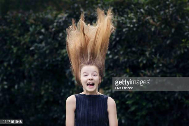 offbeat portrait of girl (12-13) in a back yard with tangled long fair hair blowing up above her - tousled hair stock pictures, royalty-free photos & images