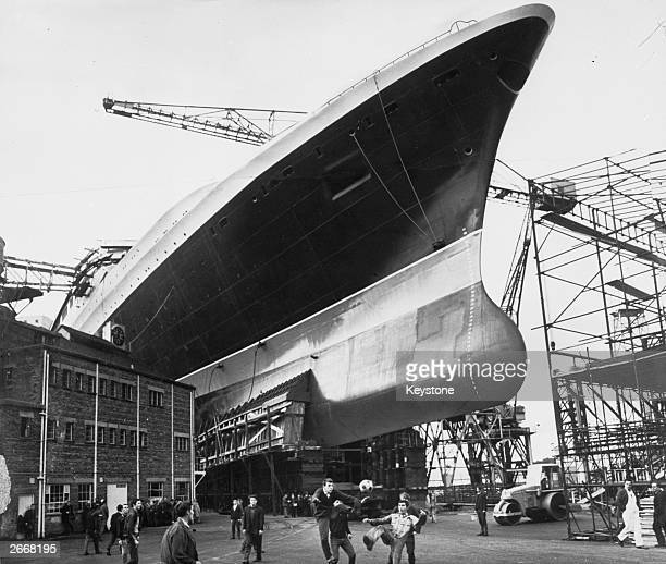 Offduty shipyard workers take part in a game of soccer beneath the bows of the new 30 million Cunard liner Q4 at the John Brown Co shipyard Clydebank...