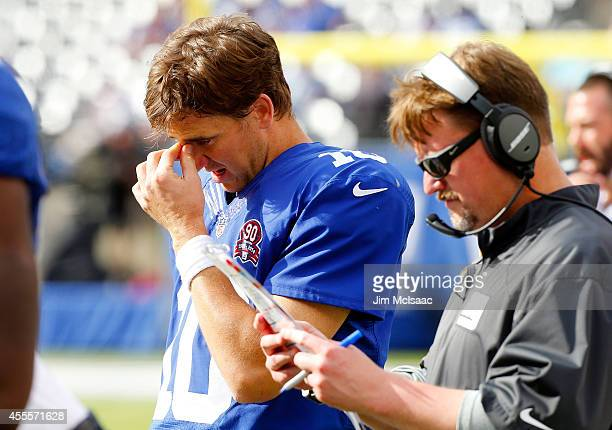 Offensive coordinator Ben McAdoo and Eli Manning of the New York Giants stand on the sidelines late in a game against the Arizona Cardinals on...