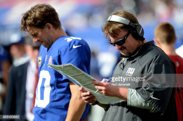Offensive coordinator Ben McAdoo and quarterback Eli Manning of the New York Giants look on from the sideline against the Arizona Cardinals during a...
