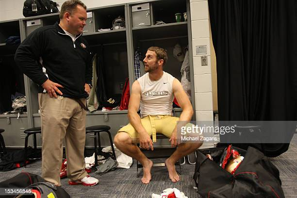 Offensive Coordinator Greg Roman of the San Francisco 49ers talks with Alex Smith in the locker room following the game against the New York Jets at...