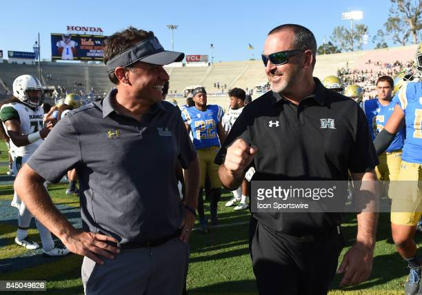 UCLA offensive coordinator Jedd Fisch talks with Hawai'i head coach Nick Rolovich during a college football game between the Hawai'i Rainbow Warriors...