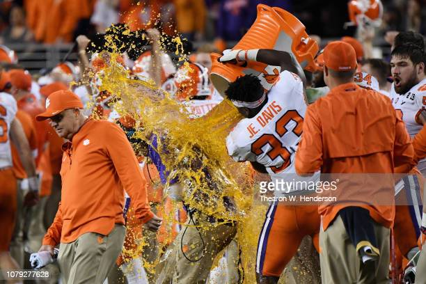Offensive coordinator Jeff Scott has gatorade dumped on him by JD Davis of the Clemson Tigers after their 4416 win over Alabama Crimson Tide in the...