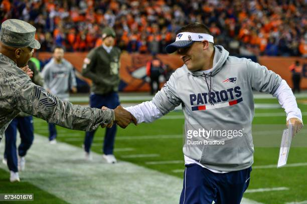 Offensive coordinator Josh McDaniels shakes hands with a member of the armed forces on the field before a game between the Denver Broncos and the New...