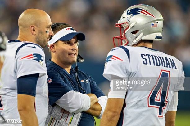 Offensive coordinator Josh McDaniels talks with Jarrett Stidham and Brian Hoyer of the New England Patriots during a week two preseason game against...