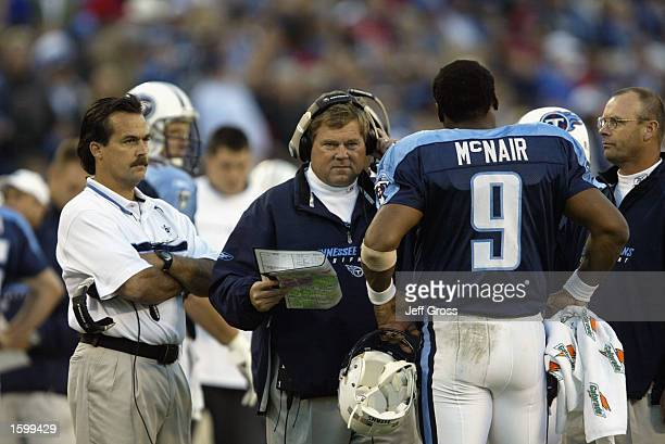 Offensive Coordinator Mike Heimerdinger and Head Coach Jeff Fisher of the Tennessee Titans talk with quarterback Steve McNair during their NFL game...