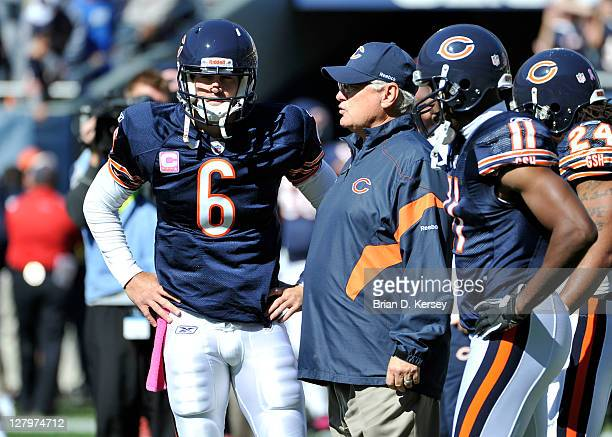 Offensive coordinator Mike Martz of the Chicago Bears talks with quarterback Jay Cutler before the game against the Carolina Panthers at Soldier...