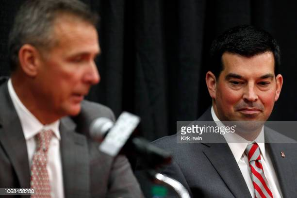 Offensive coordinator Ryan Day of the Ohio State Buckeyes listens as head coach Urban Meyer answers a question during a press conference at Ohio...