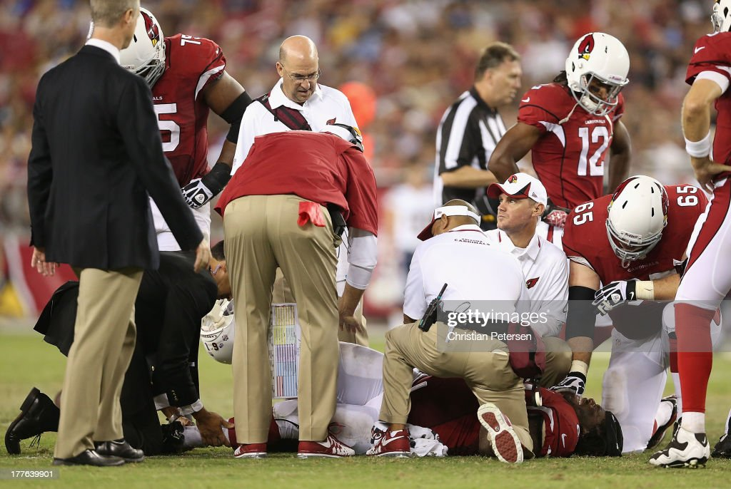 Offensive guard Jonathan Cooper #61 of the Arizona Cardinals is looked at by trainers and the team doctor after he broke his left fibula while attempting a tackle against the San Diego Chargers during the preseason NFL game at the University of Phoenix Stadium on August 24, 2013 in Glendale, Arizona.