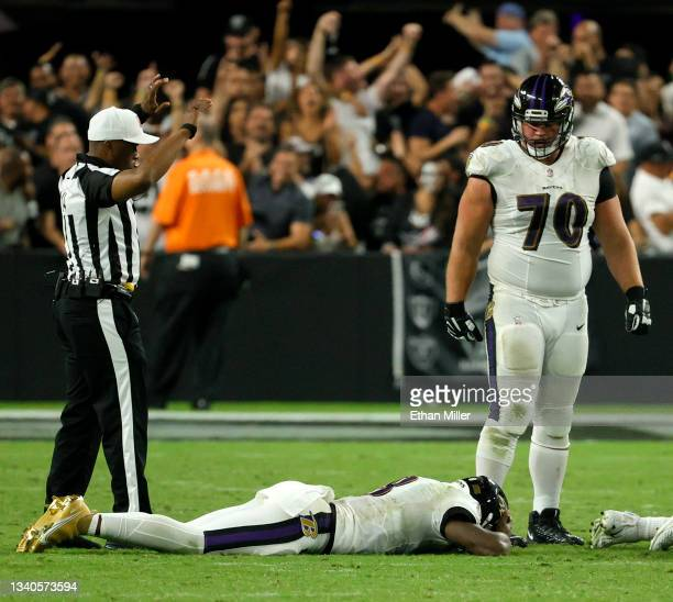 Offensive guard Kevin Zeitler of the Baltimore Ravens looks at quarterback Lamar Jackson of the Baltimore Ravens as he lies on the field after his...