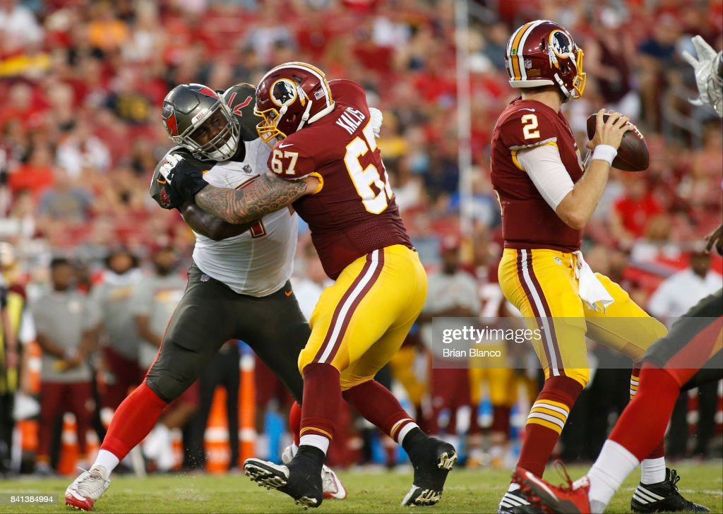 Offensive guard Kyle Kalis #67 of the Washington Redskins protects quarterback Nate Sudfeld #2 from defensive tackle Channing Ward #71 of the Tampa Bay Buccaneers during the first quarter of an NFL preseason football game on August 31, 2017 at Raymond James Stadium in Tampa, Florida.