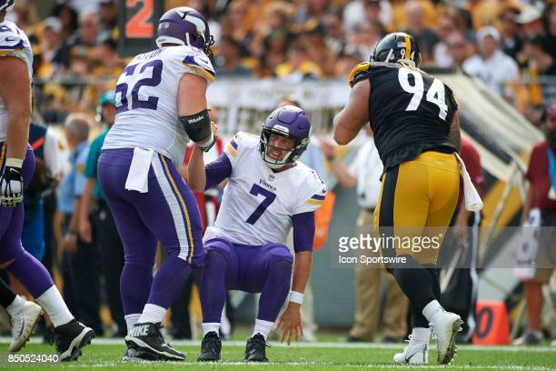 Offensive guard Nick Easton of the Minnesota Vikings helps quarterback Case Keenum of the Minnesota Vikings get up after a tackle during an NFL...