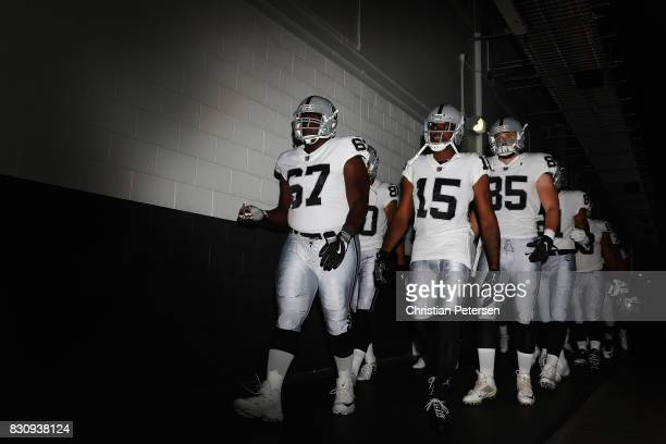 Offensive guard Oni Omoile, wide receiver Michael Crabtree and tight end Ryan O'Malley of the Oakland Raiders lead teamamtes onto the field before...
