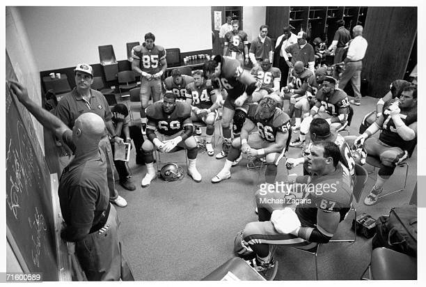 Offensive line coach Bobb McKittrick of the San Francisco 49ers writes on the chalkboard as players look on before the game against the Dallas...