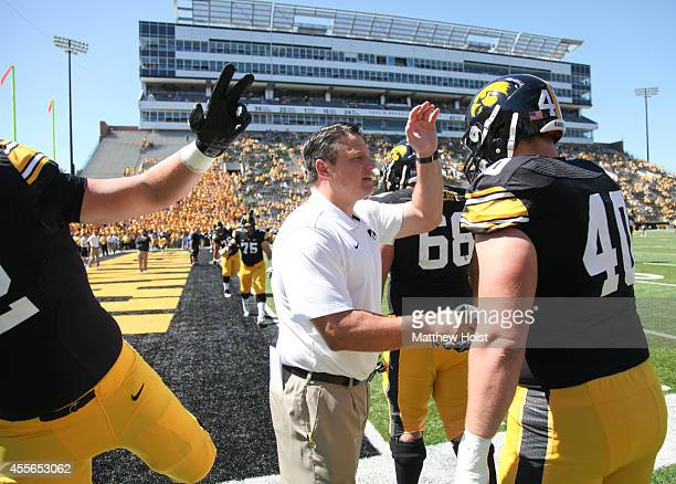 Offensive line coach Brian Ferentz talks with linebacker Parker Hesse of the Iowa Hawkeyes before the matchup against the Ball State Cardinals on...