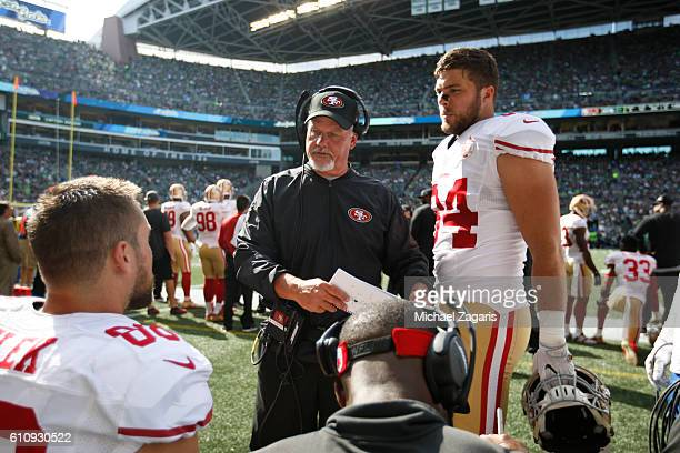 Offensive Line Coach Pat Flaherty of the San Francisco 49ers talks with Garrett Celek and Blake Bell on the sideline during the game against the...