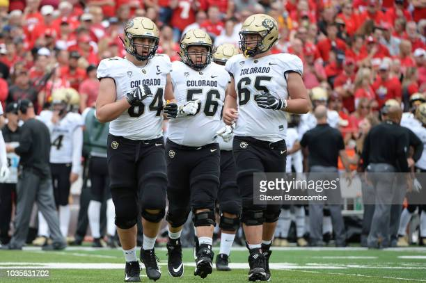 Offensive lineman Aaron Haigler of the Colorado Buffaloes and offensive lineman Tim Lynott and offensive lineman Colby Pursell take the field against...
