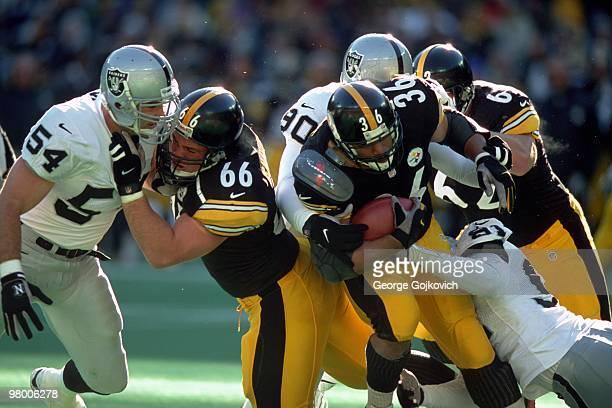 Offensive lineman Alan Faneca blocks linebacker Greg Biekert of the Oakland Raiders as running back Jerome Bettis tries to gain yards against...