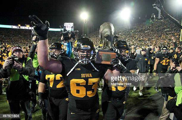 Offensive lineman Austin Blythe and defensive end Melvin Spears of the Iowa Hawkeyes carry The Floyd of Rosedale trophy off the field after defeating...