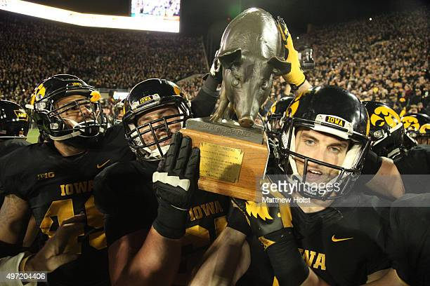 Offensive lineman Austin Blythe and kicker Marshall Koehn of the Iowa Hawkeyes carry The Floyd of Rosedale trophy off the field after defeating the...