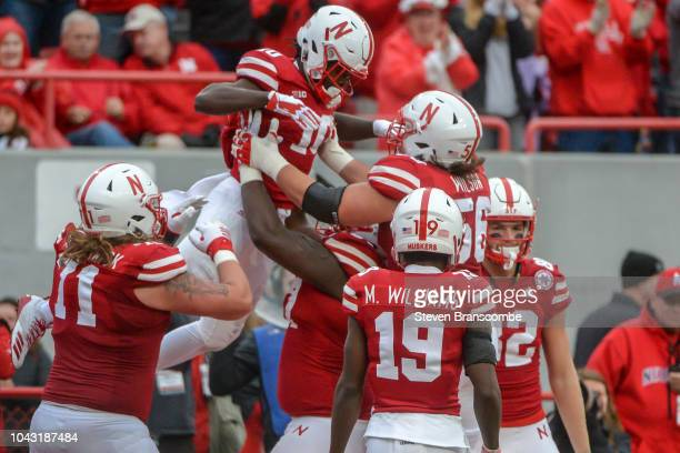 Offensive lineman Boe Wilson of the Nebraska Cornhuskers lifts wide receiver JD Spielman after a touchdown against the Purdue Boilermakers at...