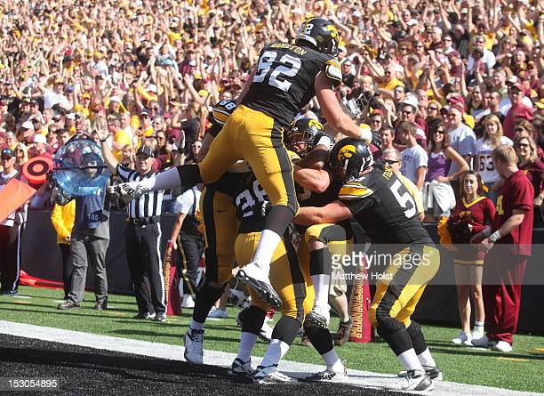 Offensive lineman Brandon Scherff fullback Brad Rogers tight end Ray Hamilton and center James Ferentz of the Iowa Hawkeyes pile onto fullback Mark...