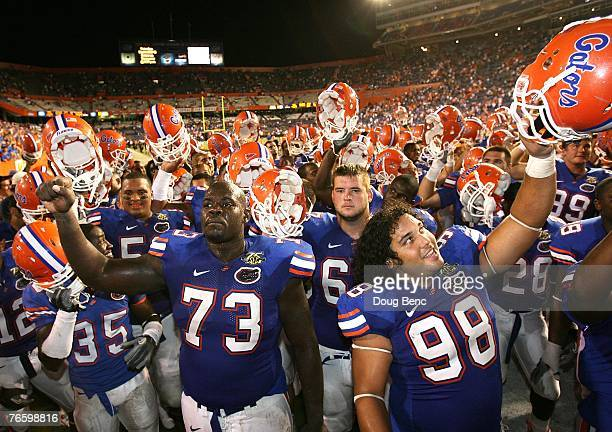 Offensive lineman Carlton Medder and defensive tackle Clint McMillan of the Florida Gators celebrate with fans after defeating the Troy Trojans at...