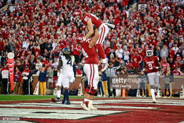Offensive lineman Cody Ford and tight end Grant Calcaterra of the Oklahoma Sooners celebrate a touchdown against the West Virginia Mountaineers at...