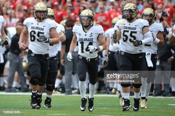 Offensive lineman Colby Pursell of the Colorado Buffaloes and wide receiver Jay MacIntyre and offensive lineman Brett Tonz lead the team on the field...