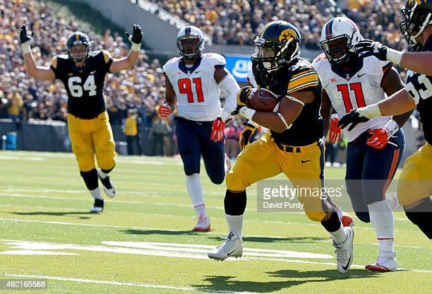 Offensive lineman Cole Croston of the Iowa Hawkeyes signals touchdown as his teammate running back Derrick Mitchell Jr #32 of the Iowa Hawkeyes...