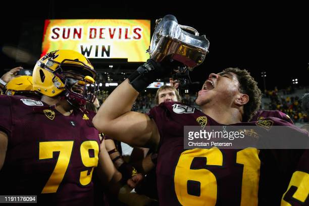 Offensive lineman Dohnovan West of the Arizona State Sun Devils celebrates with the Territorial Cup following the NCAAF game against the Arizona...