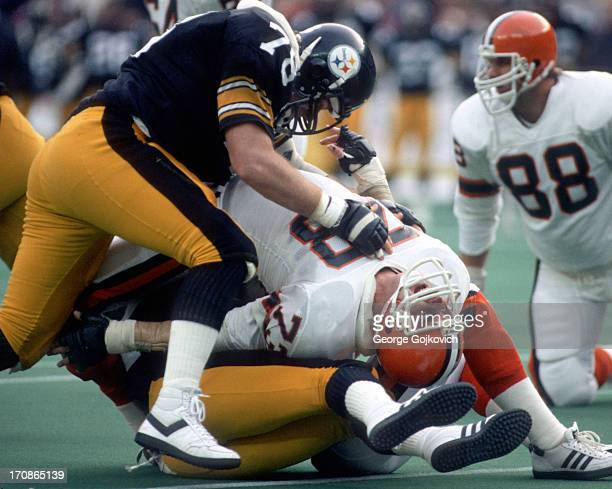 Offensive lineman Doug Dieken of the Cleveland Browns is sandwiched between defensive lineman Mark Catano of the Pittsburgh Steelers and another...