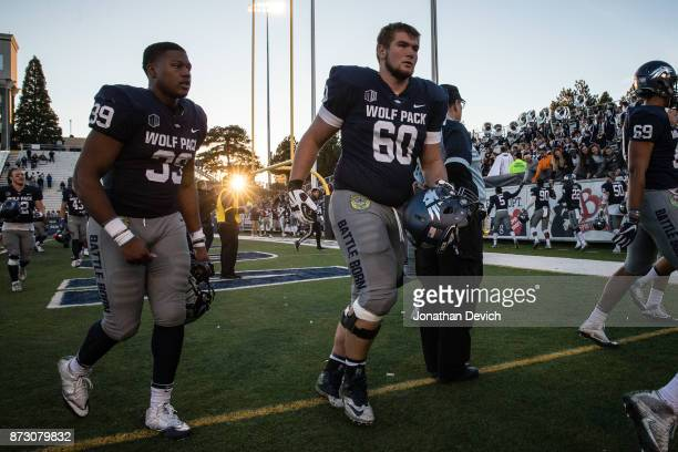 Offensive lineman Dylan Porter of the Nevada Wolf Pack and defensive end Ricky Thomas Jr #39 of the Nevada Wolf Pack walk off the field after winning...