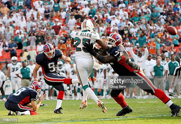 Offensive lineman Jason Peters of the Buffalo Bills blocks out cornerback Will Allen of the Miami Dolphins as place kicker Rian Lindell kicks the...