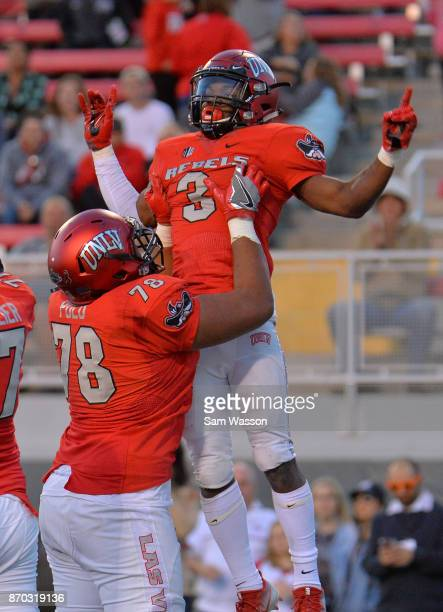 Offensive lineman Justin Polu and running back Lexington Thomas of the UNLV Rebels celebrate after Thomas scored a touchdown during their game at Sam...