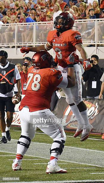 Offensive lineman Justin Polu of the UNLV Rebels celebrates with teammate running back Lexington Thomas after he scored a touchdown against the...