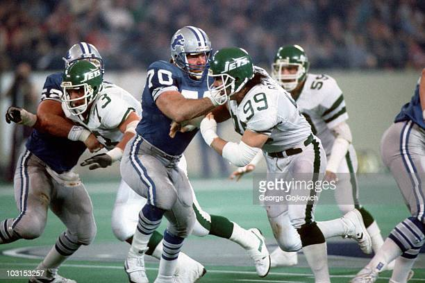 Offensive lineman Keith Dorney of the Detroit Lions blocks defensive lineman Mark Gastineau of the New York Jets as teammate Steve Mott blocks Joe...