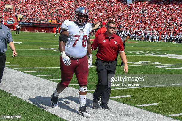 Offensive lineman Kirk Kelley of the Troy Trojans walks off the field after an injury against the Nebraska Cornhuskers at Memorial Stadium on...