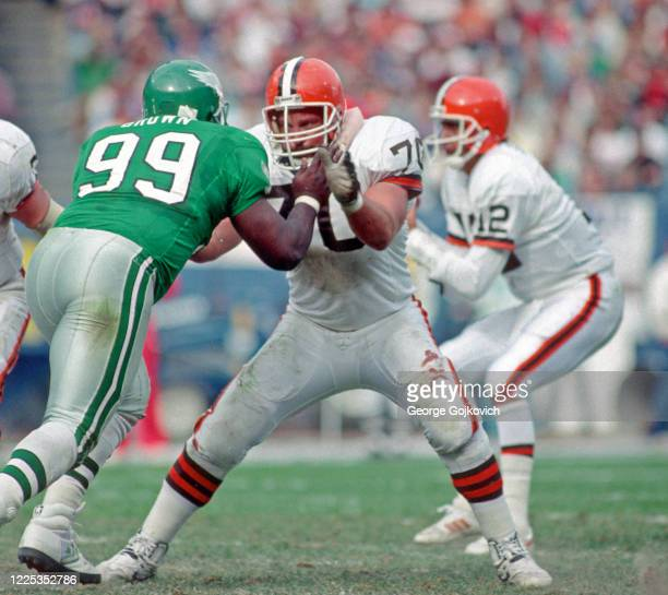 Offensive lineman Larry Williams of the Cleveland Browns blocks against defensive lineman Jerome Brown of the Philadelphia Eagles as quarterback Don...