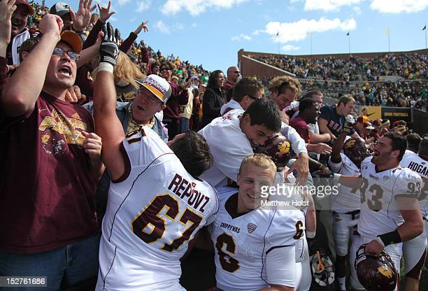Offensive lineman Mike Repovz running back Saylor Lavalli and defensive lineman Joe Kinville of the Central Michigan Chippewas celebrate with fans...