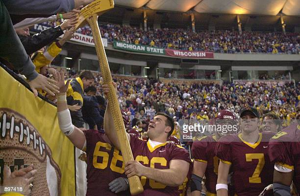 Offensive lineman Ryan Roth of the Minnesota Golden Gophers lets a fan touch Paul Bunyan's Axe trophy of the longest continuous rivalry in Division...