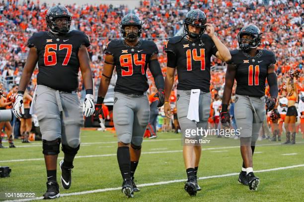 Offensive lineman Shane Richards defensive end Jordan Brailford quarterback Taylor Cornelius and linebacker Amen Ogbongbemiga of the Oklahoma State...