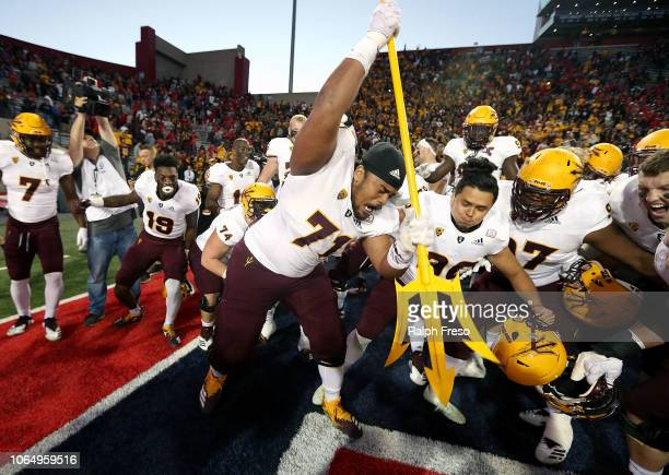 Offensive lineman Steven Miller of the Arizona State Sun Devils drives a pitchfork into the turf as he celebrates with teammates following a 4140...