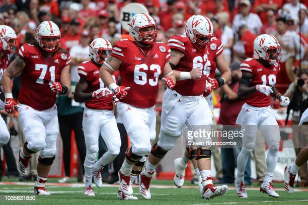 Offensive lineman Tanner Farmer of the Nebraska Cornhuskers leads the team on the field against the Colorado Buffaloes at Memorial Stadium on...