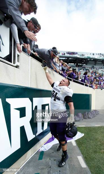 Offensive lineman Tommy Doles of the Northwestern Wildcats celebrates with fans after a 2919 win over Michigan State at Spartan Stadium on October 6...