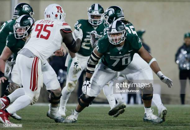 Offensive lineman Tyler Higby of the Michigan State Spartans moves to block defensive lineman Jon Bateky of the Rutgers Scarlet Knights during the...